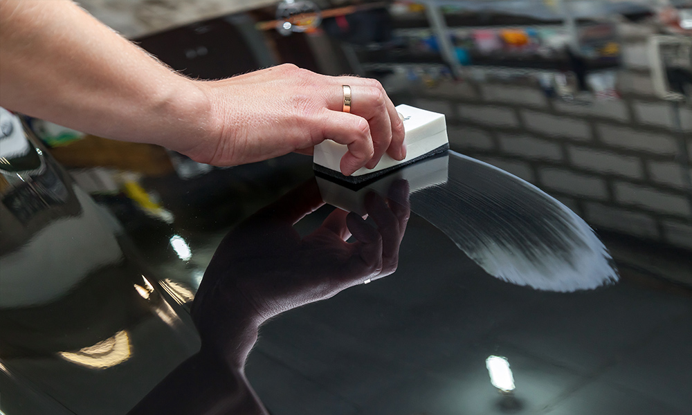 A hand using ceramic tool for application on a car hood